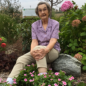 Image of Carol Jackubs sitting in a bed of flowers