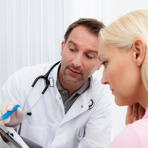 woman sitting while doctor explains paperwork