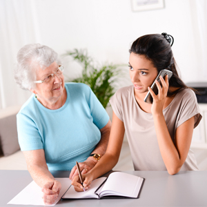 young woman helping senior woman make phone call