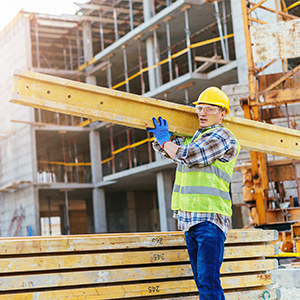 Image of construction worker lifting heavy metal beam