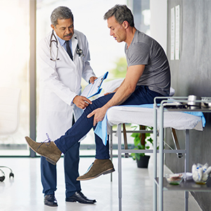 Physician examining knee of worker