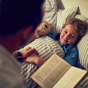 Image of father reading to daughter