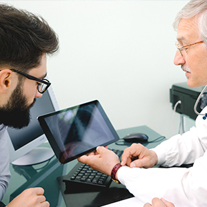 Image of Physician Showing Lung Xray on Tablet to Younger Male Patient