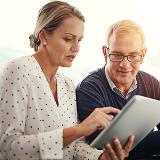 middle-aged woman looking at tablet with middle-aged man