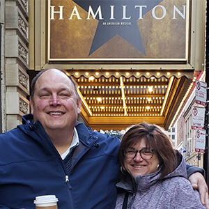 smiling couple standing under advertisement for a musical