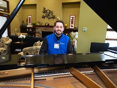 Social worker Brandon Pierce playing piano at Merlin and Carolyn Hanson Hospice Center