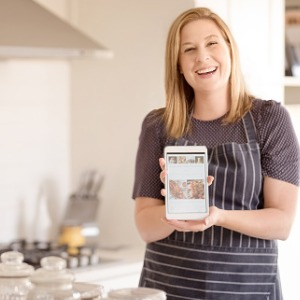 female-food-blogger-in-apron-showing-a-digital-tablet-with-her-picture-id1091555728