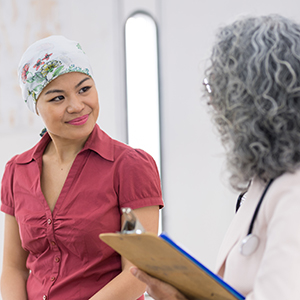 Lady in head scarf smiling and talking to doctor