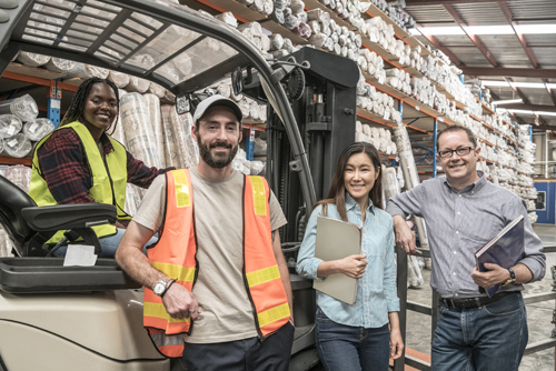Image of employees smiling around fork lift