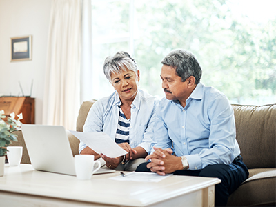 man and woman sitting on sofa reviewing paperwork