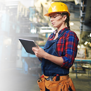 Female worker with hardhat and iPad in industrial building