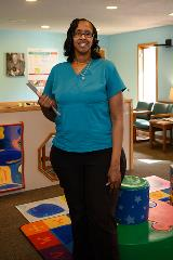 smiling woman standing in pediatric waiting room