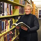 woman standing against a shelf of books
