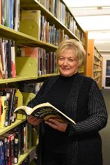 woman standing against shelf of books