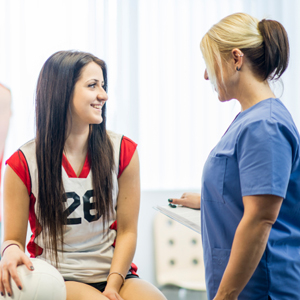 teen holding volleyball with doctor