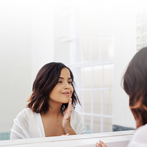 woman applying skin care product in mirror