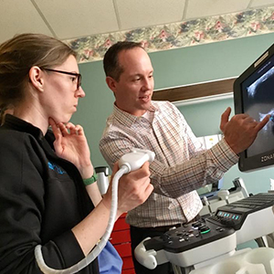 Image of man explaining ultrasound to woman