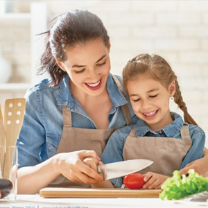 Image of mother cutting tomato with daughter