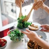 Image of person placing salad on plate