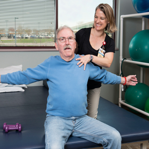 Man doing back stretches with trainer